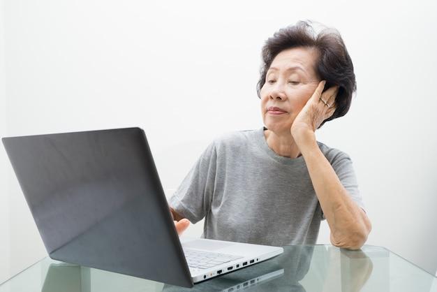 Bejaarde dame die met laptop werkt, die met laptop werkt