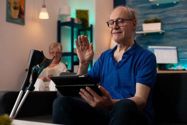 Bejaarde die bij tablet met videogesprekconferentie zwaait