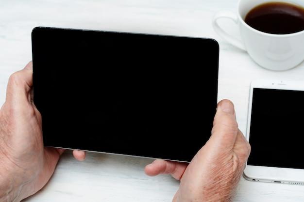 Bejaarde die digitale tablet met kop van koffie en mobiele telefoon houdt