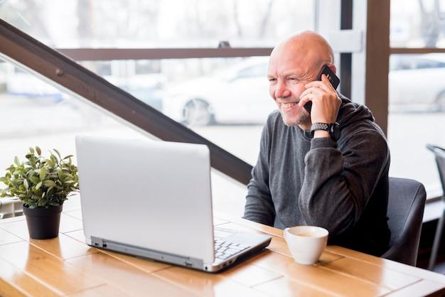Bejaarde die door mobiele telefoon spreekt