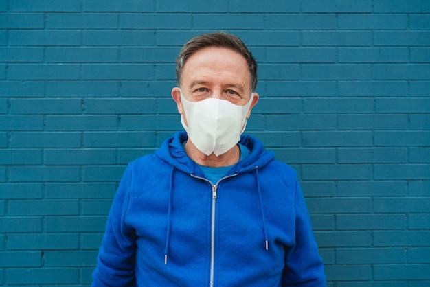Bejaarde die een medisch masker draagt en voor een blauwe muur staat