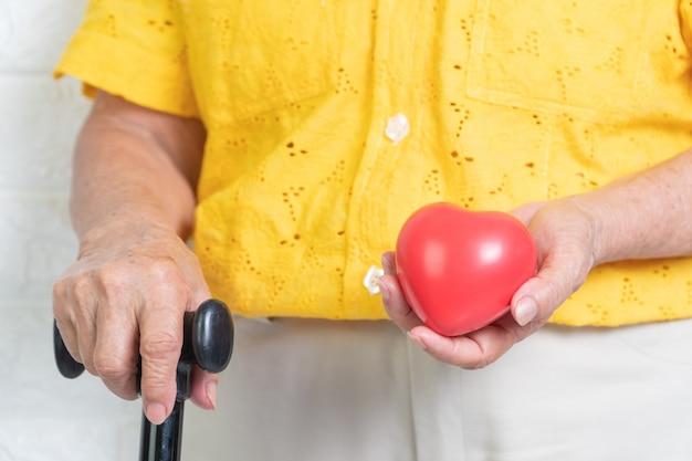 Bejaarde die een stok en een rood hart houdt.