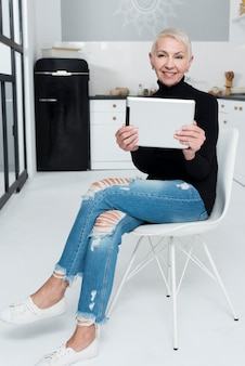 Bejaarde die en met tablet in de keuken glimlacht stelt