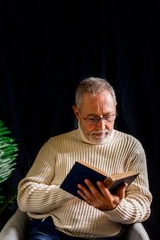 Bejaarde die in glazen boek leest