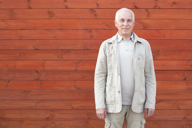 Bejaarde die in openlucht op houten muurachtergrond glimlachen, gelukkige succesvolle zakenman.
