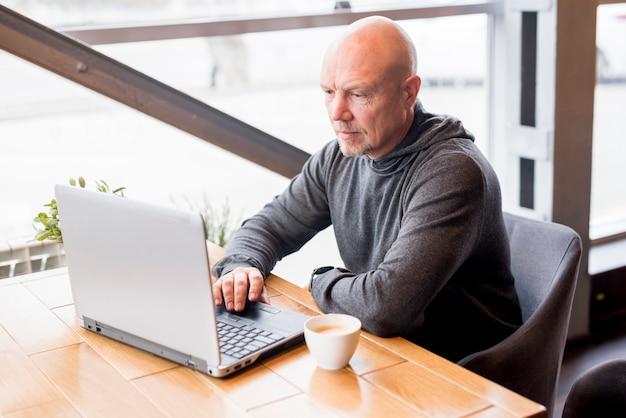 Bejaarde die laptop met behulp van