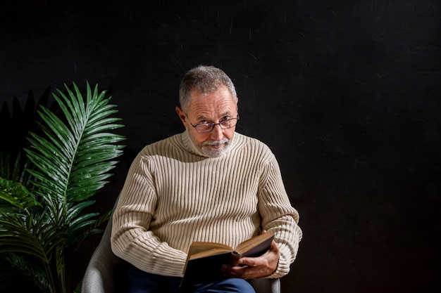 Bejaarde die met boek camera bekijkt