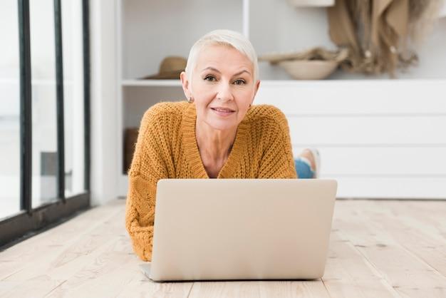 Bejaarde die met laptop glimlacht