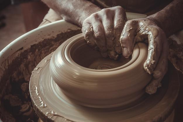 Bejaarde die pot maakt die aardewerkwiel in studio met behulp van. detailopname.