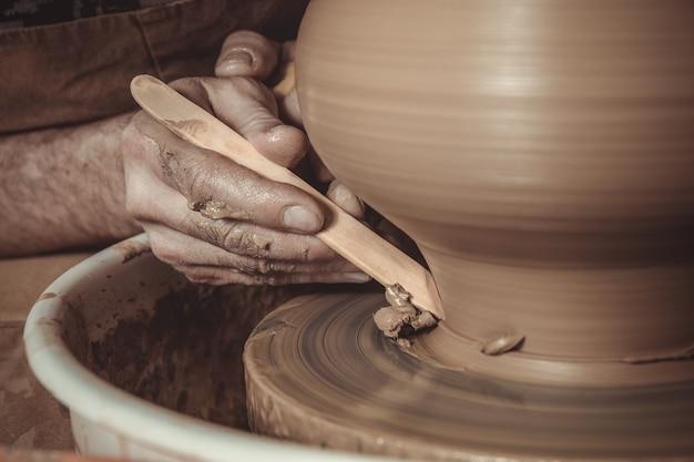 Bejaarde die pot maakt die aardewerkwiel in studio met behulp van