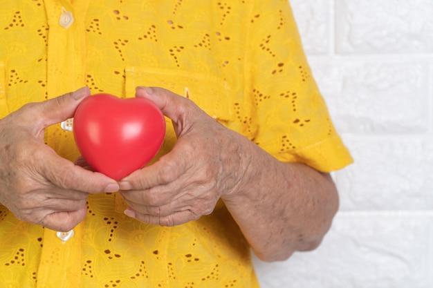 Bejaarde die rood hart houdt.