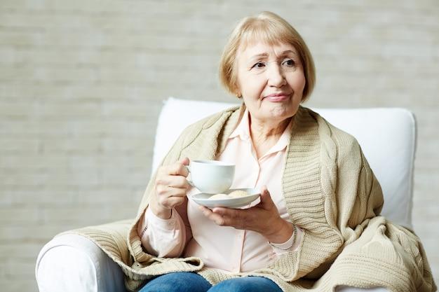 Bejaarde die van thee geniet