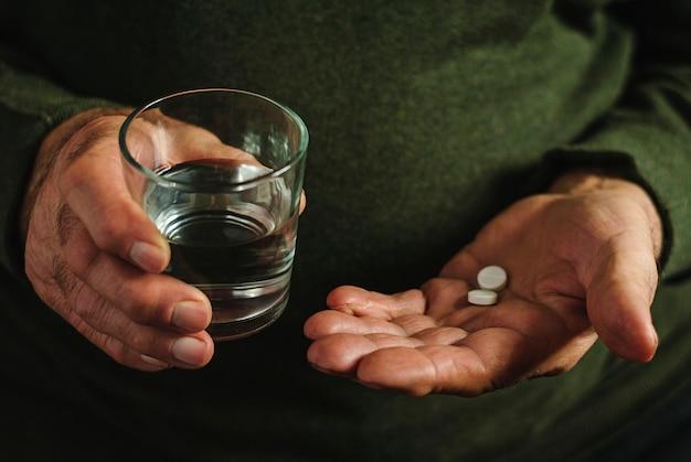 Bejaarde die zijn medicijn, twee tabletten neemt.