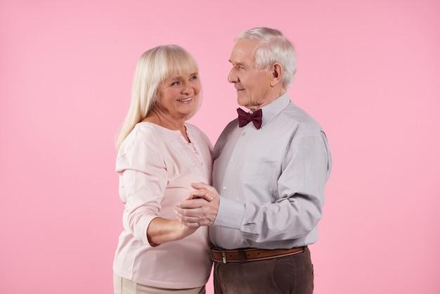 Bejaarde echtpaar dansen geïsoleerd op roze.