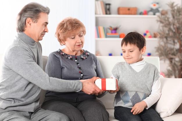 Bejaarde echtpaar geeft een geschenk aan hun kleinzoon op zijn verjaardag.