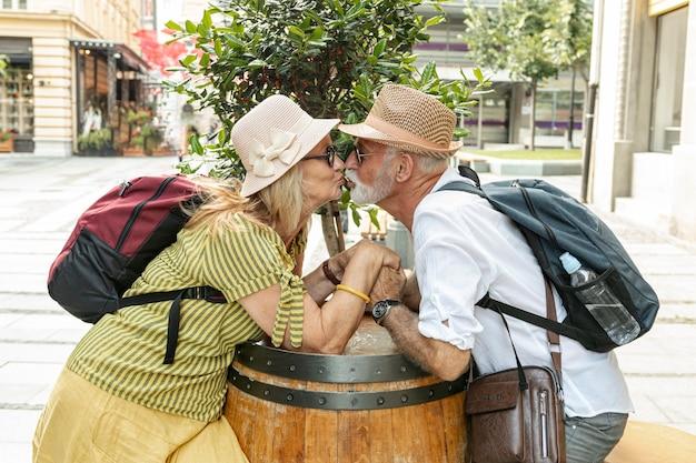 Bejaarde echtpaar hand in hand tijdens het kussen