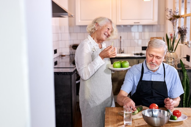 Bejaarde echtpaar in de keuken thuis, senior man in schort zit carving verse groenten, grijsharige vrouw appels in handen houden en praten met hem