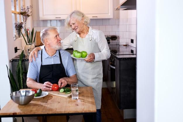 Bejaarde echtpaar in de keuken thuis, senior man in schort zit snijwerk van verse groenten, grijsharige vrouw appels in handen houden en praten met hem
