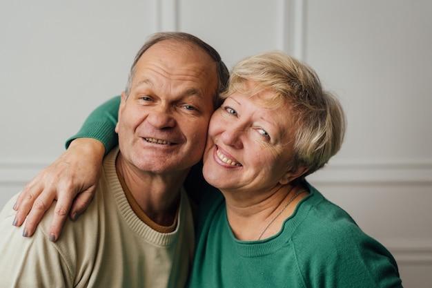 Bejaarde echtpaar knuffelen en glimlachen.