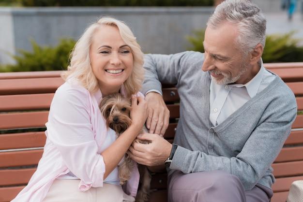 Bejaarde echtpaar loopt op het plein met haar kleine hond.