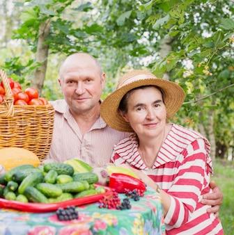 Bejaarde echtpaar met groenten buiten