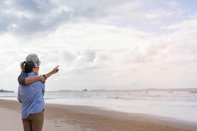 Bejaarde echtpaar omarmd aan de kust