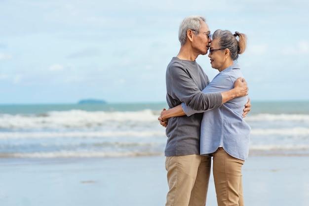 Bejaarde echtpaar omarmd en kussen aan zee