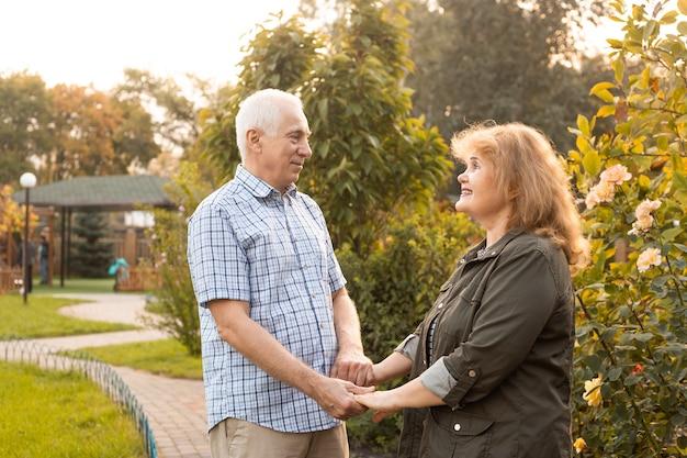 Bejaarde echtpaar omarmen in de lente of zomer park, valentijnsdag