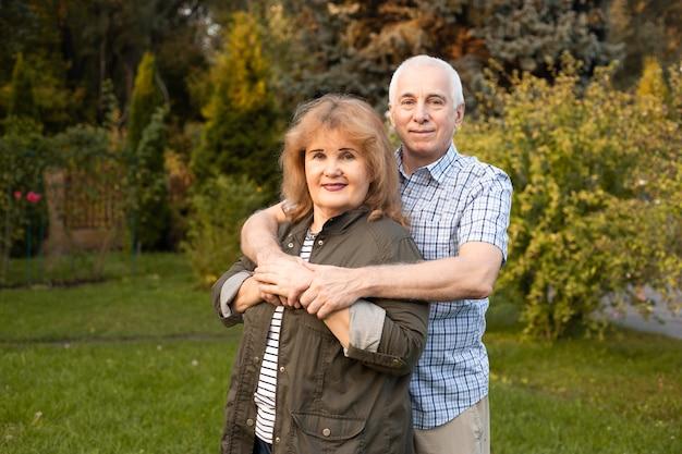 Bejaarde echtpaar omarmen in de lente of zomer park