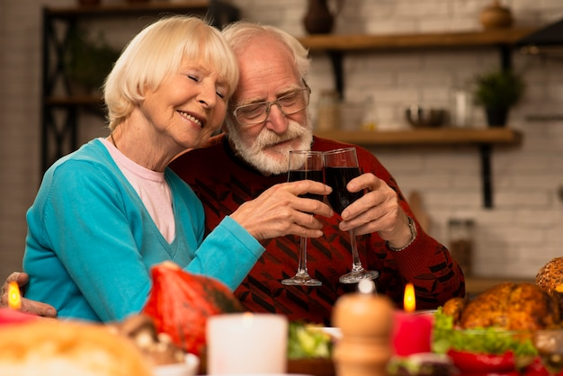 Bejaarde echtpaar roosterende glazen samen