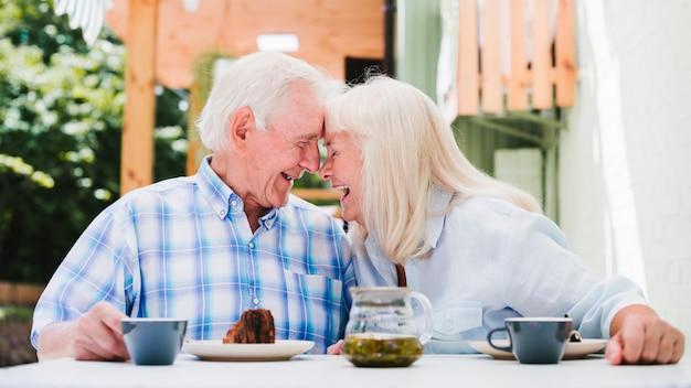 Bejaarde echtpaar zitten kop aan kop thee drinken