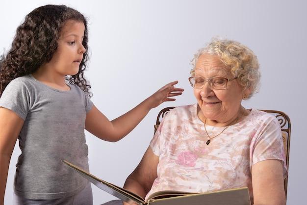 Bejaarde en kind die een boek op grijs lezen