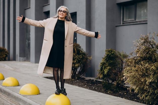 Bejaarde gelukkige vrouw die in de straat loopt