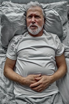 Bejaarde gepensioneerde man liggend in bed met geopende ogen, slaapproblemen. ongelukkige rijpe oude grootvader die 's nachts aan slapeloosheid lijdt.