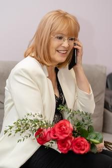 Bejaarde glimlachende vrouw die telefonisch gefeliciteerd met haar verjaardag ontvangt