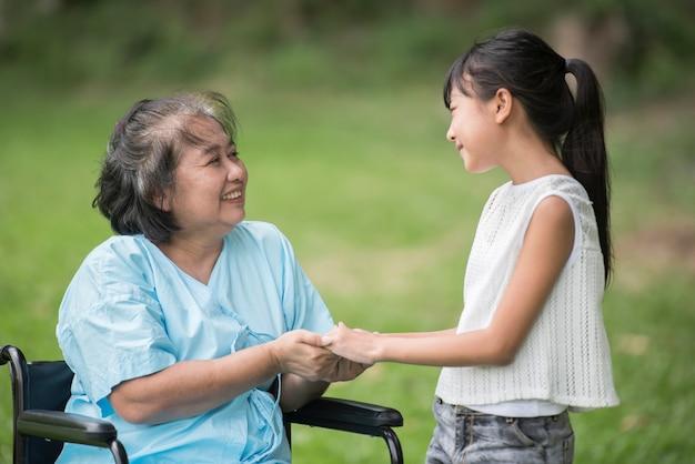 Bejaarde grootmoeder in rolstoel met kleindochter in de het ziekenhuistuin