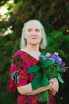 Bejaarde grootmoeder met een boeket bloemen in het park.