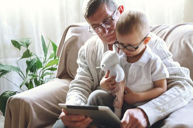 Bejaarde grootvader en zijn kleine kleinzoon gebruiken een tablet