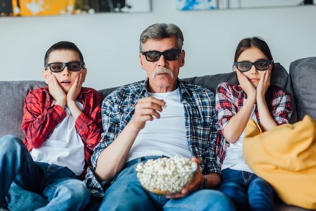 Bejaarde grootvader zit met zijn kleinkinderen op de bank in de woonkamer kijken naar horrorfilm, eet popcorn.