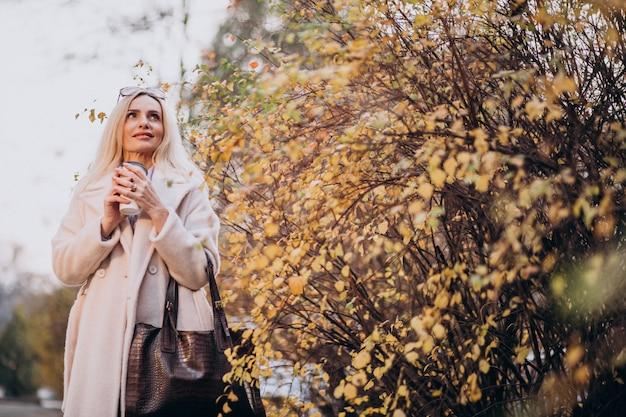 Bejaarde het drinken koffie buiten het de herfstpark