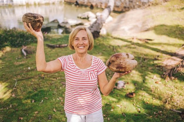 Bejaarde hogere europese reizende actieve glimlachende vrouwentoerist die genietend van in de tropische wildernis van sanya lopen. reizen langs azië, actieve levensstijl concept. hainan, china ontdekken. poseren met kokos