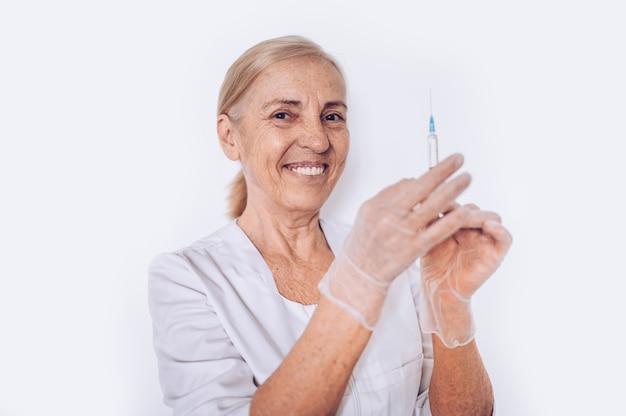 Bejaarde hogere glimlachende vrouwenarts of verpleegster met spuit in een witte medische laag en handschoenen die geïsoleerd persoonlijk beschermingsmiddel dragen. gezondheidszorg en geneeskunde concept. covid-19 pandemische crisis