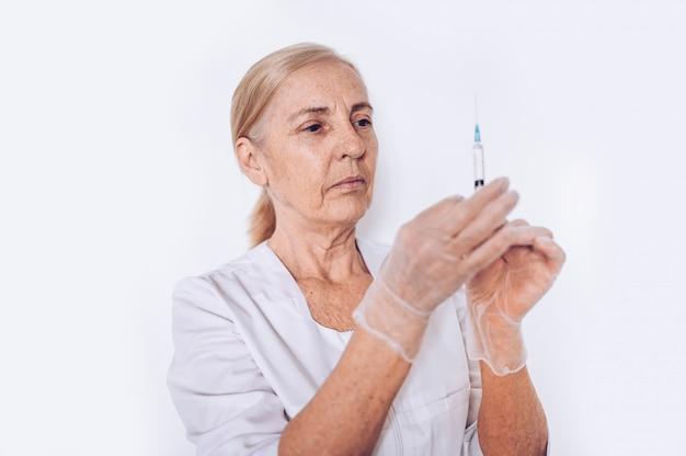 Bejaarde hogere rijpe vrouwenarts of verpleegster met spuit in een witte medische laag en handschoenen die geïsoleerd persoonlijk beschermingsmiddel dragen. gezondheidszorg en geneeskunde concept. covid-19 pandemische crisis