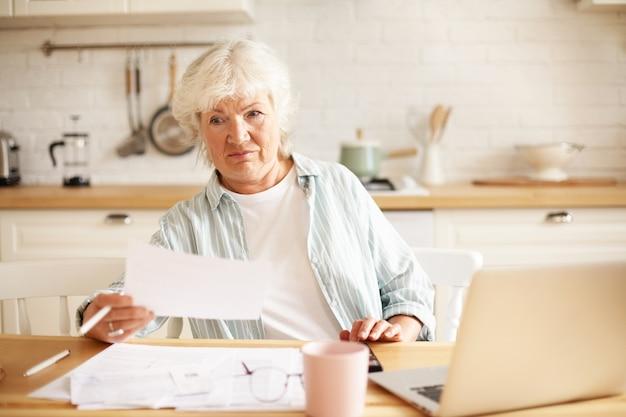 Bejaarde huisvrouw met grijze haren zitten in de keuken met open laptop en papieren op tafel, met emotionele gefrustreerde gezichtsuitdrukking, geschokt door schuldbedrag tijdens het online betalen van binnenlandse rekeningen