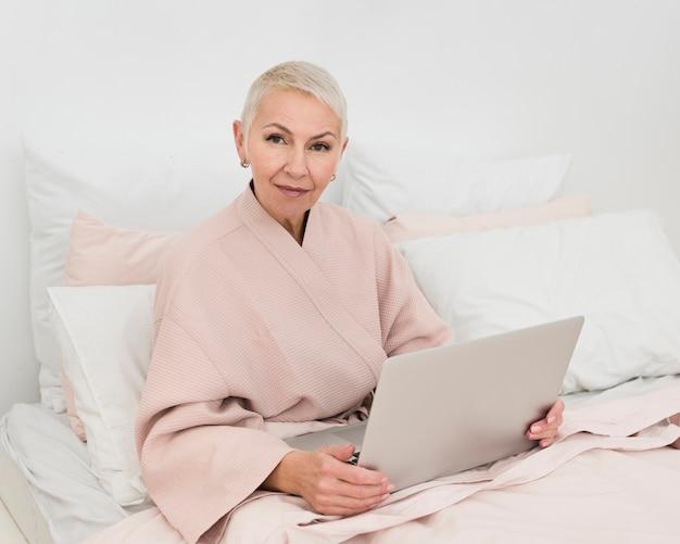 Bejaarde in badjas het stellen in bed terwijl het houden van laptop