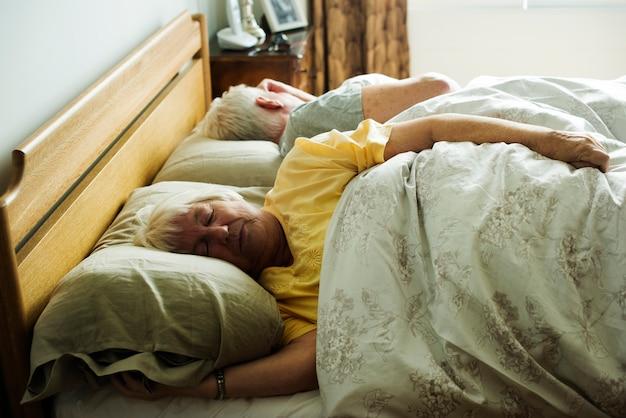 Bejaarde kaukasische paarslaap op het bed