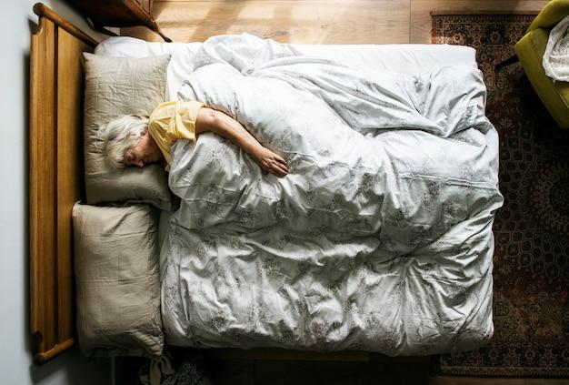 Bejaarde kaukasische vrouwenslaap op het bed