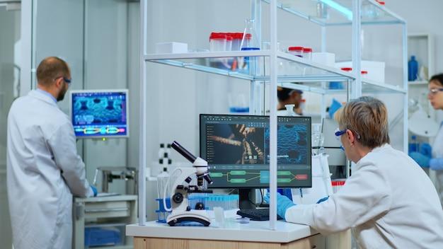 Bejaarde laboratoriumtechnicus die farmaceutisch onderzoek doet naar antibiotica, ziekte geneest met dna-versterkende medicijnen. multi-etnisch team onderzoekt virusevolutie met behulp van hightech voor behandeling tegen covid19