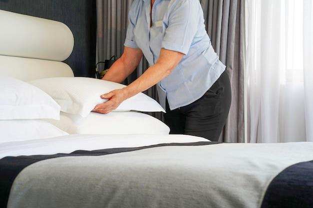 Bejaarde meid die bed in hotelruimte maakt. huishoudster bed opmaken