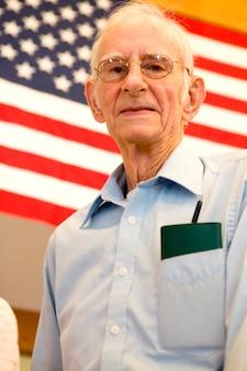 Bejaarde met amerikaanse vlag en chequeboek